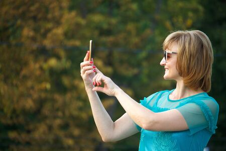 Adult middle-aged business woman on the street makes selfie on smartphone, selective focus Stok Fotoğraf - 130499307