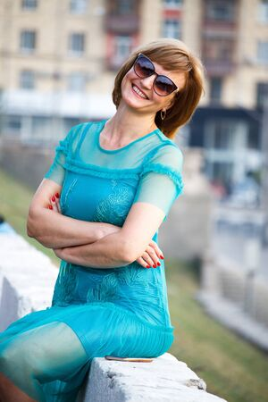 A middle aged adult woman sits in the background of the city on a stone parapet and smiles at the camera, selective focus Stok Fotoğraf - 130383143