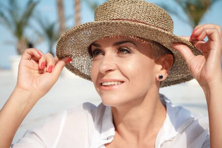 Lovely young woman with a short haircut in a beach hat on the beach, laughing and looking at the sea, the concept of a summer vacation Фото со стока