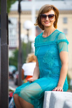 A middle aged adult woman sits in the background of the city on a stone parapet with a smartphone and smiles at the camera, selective focus