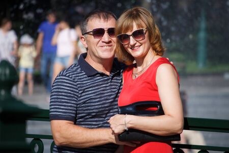 Middle aged couple smiling and hugging on a walk in a public park, on the background of the fountain, selective focus 写真素材