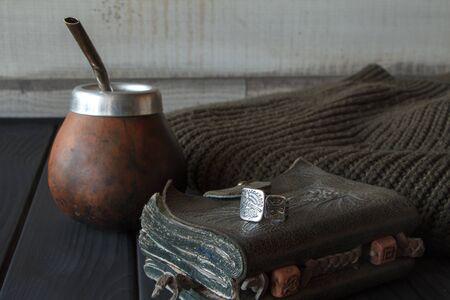 Natura morta di zucca artigianale in pelle di tè Yerba Mate realizzata a mano con paglia, quaderno in pelle, maglione e anello su tavolo verniciato nero, messa a fuoco selettiva Archivio Fotografico