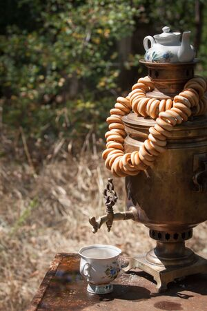 A bundle of bagels on the top of an old bronze wood burning samovar with teapot on it and a cup for tea, selective focus Banco de Imagens