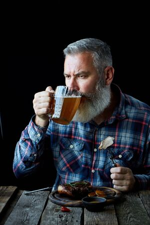 Brutal gray haired adult man with a beard eats mustard steak and drinks beer, concept of a holiday, festival, Oktoberfest or St. Patrick's Day