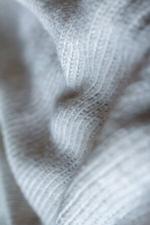 Extreme close up gray color knitted sweater made of natural wool texture, wavy folds, selective focus