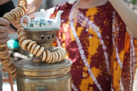 Female hands put bundle of bagels on the top of an old bronze wood burning a samovar with a teapot on it, selective focus Banco de Imagens