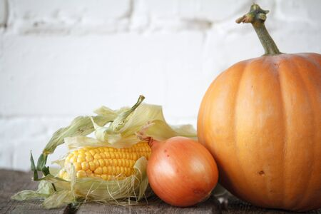 Close-up autumn pumpkin, onions and corn on wooden thanksgiving table, white brick backdrop, selective focus Stock Photo