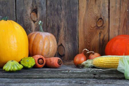 An autumn pumpkins and other vegetables on a wooden thanksgiving table, selective focus