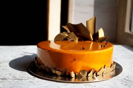 Caramel icing cake decorated with gold foil and chocolate drops on light surface, selective focus