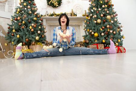 Beautiful girl in a plaid shirt and jeans sits on the background of dressed up Christmas trees with a white garland in her hands, selective focus
