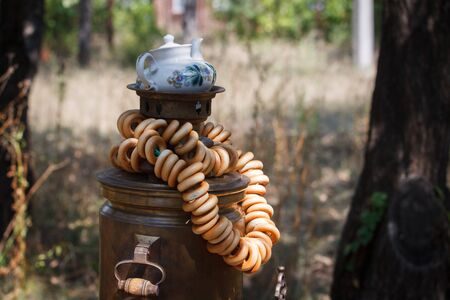 A bundle of bagels on the top of an old bronze wood burning samovar with teapot on it, selective focus
