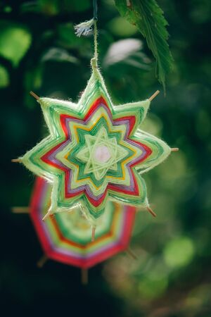 Close up of two hand made mandalas of woolen threads hanging on tree branches in the autumn forest, selective focus Stok Fotoğraf