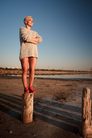 Adult middle aged blonde woman stands on a pier pillar on an old sea beach and looks at the sea, selective focus