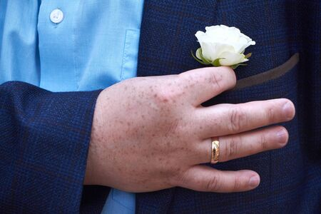 Close up of a white rose buttonhole in a pocket of a blue suit jacket, selective focus
