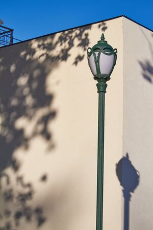 Street lamp and its shadow on white wall background