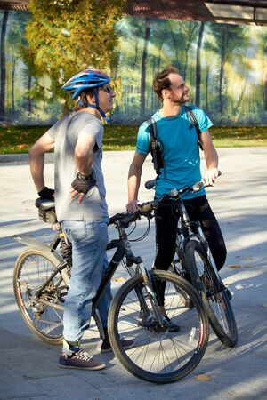 Kharkiv, Ukraine - October 14, 2019: Two male cyclists dying and talking in a city park 에디토리얼