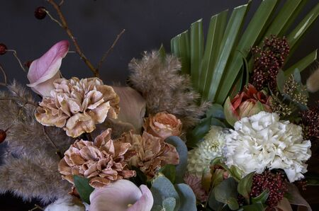 Close-up detail of a vintage bouquet in a round box on a dark background, selective focus