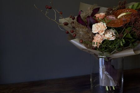 Close-up bouquet in a glass vase decorated in vintage style on a dark background, selective focus