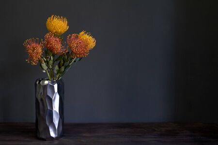 Bouquet of yellow and orange exotic protea flowers in metal vase on a dark background, selective focus