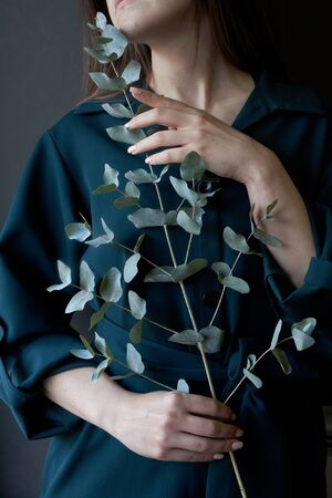 Portrait of girl in a green dress holding a eucalyptus branch on a dark background, selective focus