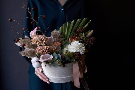 Female hands holding a box with a vintage bouquet on dark background, selective focus