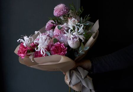 Male hands holding a bouquet decorated in vintage style on dark background, selective focus Reklamní fotografie