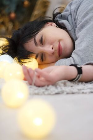 Happy attractive brunette girl lying at home with garland of white lights, selective focus