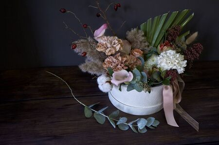 Box with a vintage bouquet and the eucalyptus branch near on a dark background, selective focus