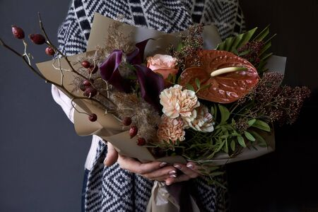 Female hands holding a bouquet decorated in vintage style on dark background, selective focus