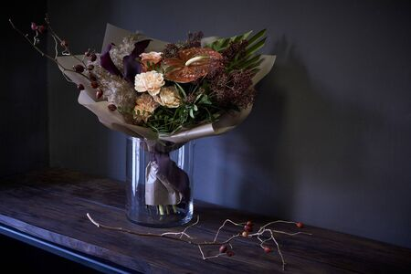 Close up bouquet in a glass vase decorated in vintage style on a dark background, selective focus