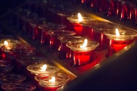 Close up of a lot of red candles in a church during a service, selective focus Stock Photo