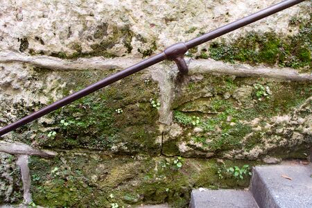 Close up of a metal railing at a medieval stone staircase covered with green moss, selective focus
