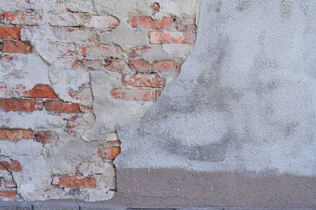 An old weathered red brick wall fragment, crumbling plaster