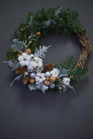 Christmas wreath made of vines decorated with fir branches, Christmas balls and natural materials, New Year concept
