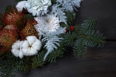 Christmas and New Year composition, Wicker basket with fir branches decorated by natural materials on dark backdrop