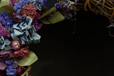 Close up detail of a vintage wreath of dried flowers in pastel colors, selective focus