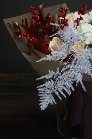 Christmas and New Year composition bouquet in a glass vase on dark background, selective focus