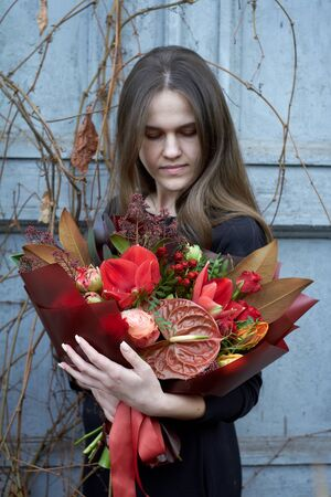 Girl holds chic autumn bouquet in red colors in vintage style outdoors on the background of dry grapes and old door, selective focus