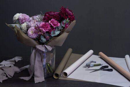 Florists desktop and purple toned bouquet in vintage style on dark background, selective focus Imagens