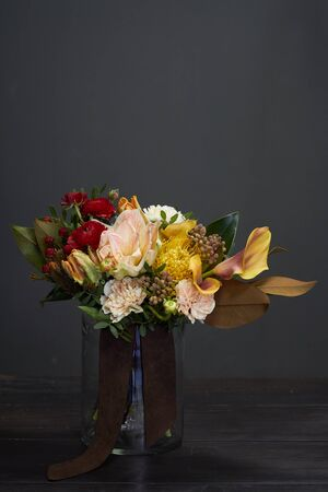 Naked bouquet in vintage style in glass vase on a dark background, selective focus