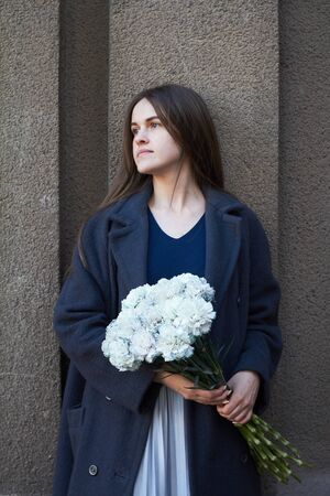 Girl with dark hair holds in her hands a bouquet of blue carnations on a gray wall background, selective focus Imagens