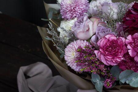Rosa und lila getönter Blumenstrauß im Vintage-Stil auf dunklem Hintergrund, selektiver Fokus Standard-Bild
