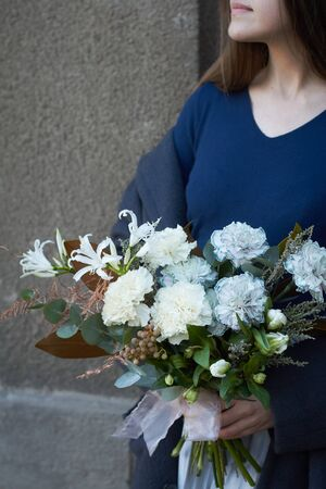 Girl holds white toned bouquet in vintage style outdoors on gray wall background, selective focus