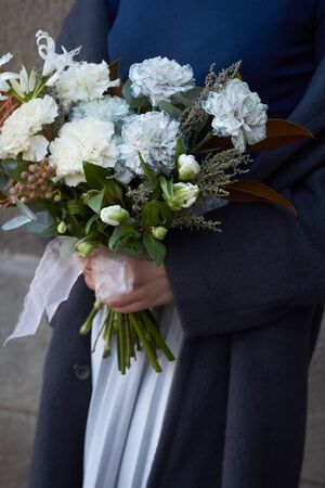 Close up female hands holds white toned bouquet in vintage style outdoors on a gray wall background, selective focus