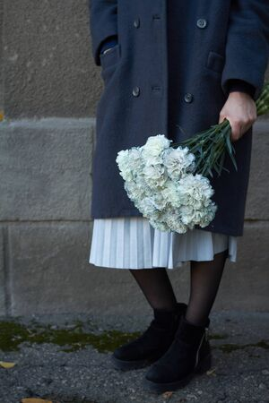 Close up female hands holds a bouquet of blue carnations on a gray wall background, selective focus