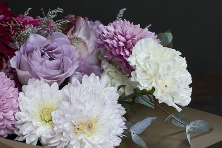 Pink and purple toned bouquet in vintage style on dark background, selective focus