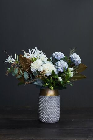 White toned bouquet in vintage style in a ceramic vase on dark background, selective focus
