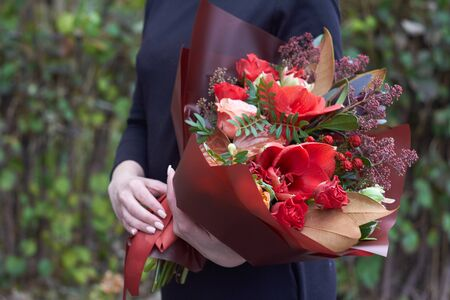 Girl holds chic autumn bouquet in red colors in vintage style outdoors opposite of park, selective focus