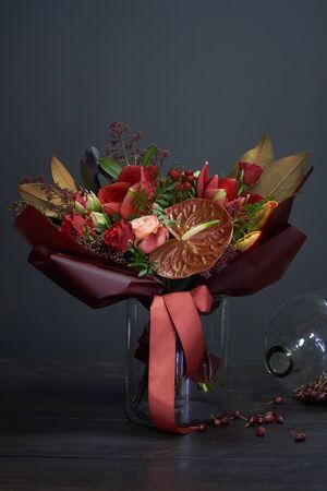 Chic autumn bouquet in red colors in vintage style in a glass vase and a huge jar of dry rose hips on dark background, selective focus Imagens