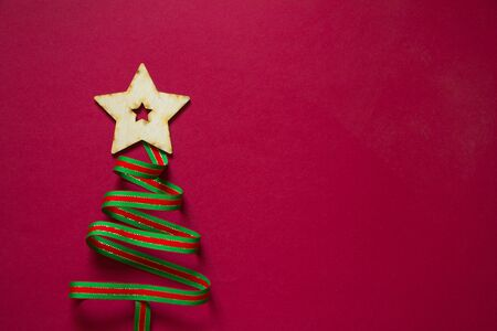 Minimal winter creative table flat lay, Christmas tree made of ribbon and wooden star figurine on a red background